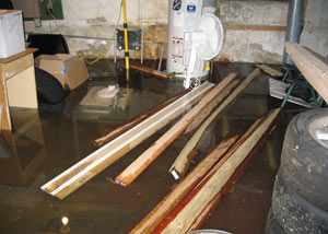 A severely flooding basement in Columbus, with lumber and personal items floating in a foot of water