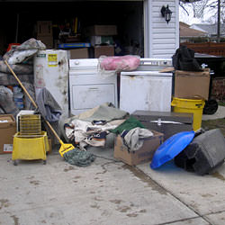 Soaked, wet personal items sitting in a driveway, including a washer and dryer in Roundup.
