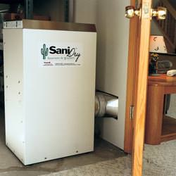 A basement dehumidifier with an ENERGY STAR® rating ducting dry air into a finished area of the basement  in Busby