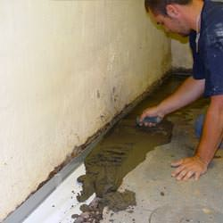 A basement waterproofer installing a perimeter drain system in White Sulphur Springs
