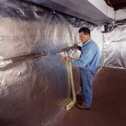 Installation of a radiant heat and vapor barrier on a basement wall in Worden