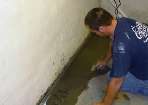 Restoring a concrete slab floor with fresh concrete after jackhammering it and installing a drain system in Hays.